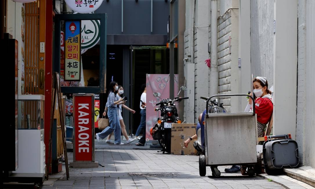 Funcionária descansa do lado de fora da loja em Seul, Coreia do Sul Foto: HEO RAN / REUTERS
